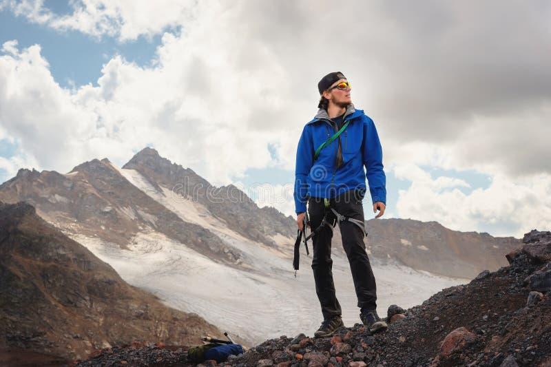 Retrato de um guia profissional de um alpinista em um tampão e em óculos de sol com um machado de gelo em sua mão contra foto de stock