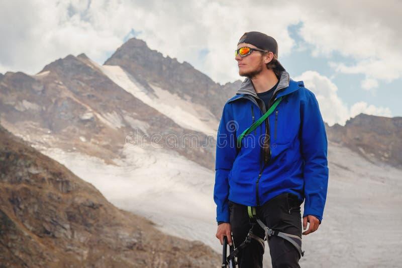 Retrato de um guia profissional de um alpinista em um tampão e em óculos de sol com um machado de gelo em sua mão contra fotos de stock royalty free