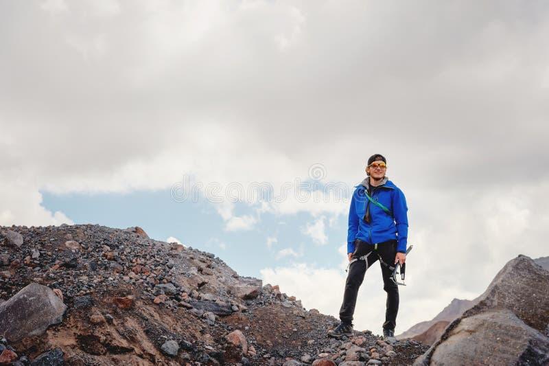 Retrato de um guia profissional de um alpinista em um tampão e em óculos de sol com um machado de gelo em sua mão contra foto de stock royalty free