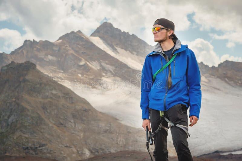 Retrato de um guia profissional de um alpinista em um tampão e em óculos de sol com um machado de gelo em sua mão contra imagem de stock