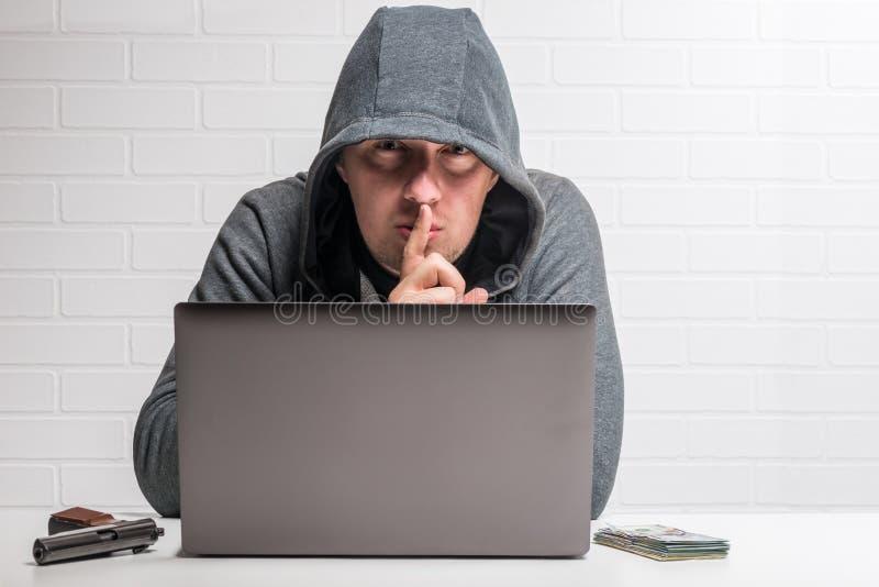 Retrato de um hacker criminoso com um conceito do caderno, da arma e do dinheiro foto de stock royalty free
