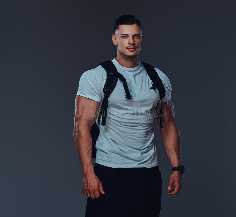 Retrato de um halterofilista considerável muscular no sportswear com a mochila que levanta contra um fundo cinzento foto de stock