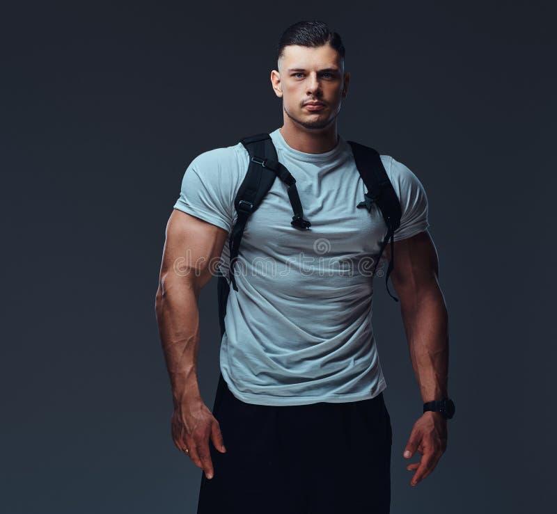 Retrato de um halterofilista considerável muscular no sportswear com a mochila que levanta contra um fundo cinzento fotografia de stock