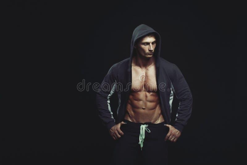 Retrato de um halterofilista muscular considerável no hoodie que levanta o ove fotos de stock royalty free