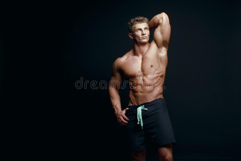 Retrato de um halterofilista muscular considerável no hoodie que levanta o ove imagem de stock royalty free