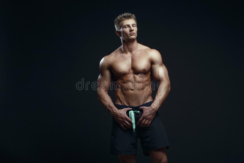 Retrato de um halterofilista muscular considerável que levanta sobre vagabundos pretos fotografia de stock royalty free