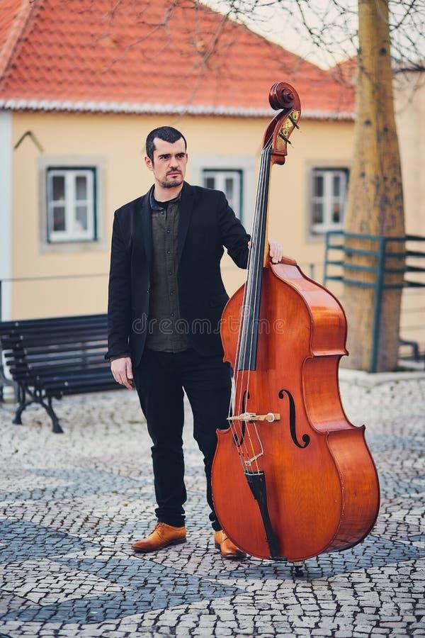 Retrato de um homem à moda com uma barba em uma rua velha com um contrabaixo Um músico contínuo com um grande instrumento musical fotografia de stock