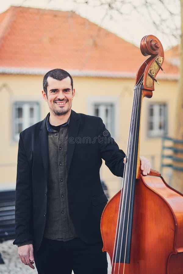 Retrato de um homem à moda com uma barba em uma rua velha com um contrabaixo Um músico contínuo com um grande instrumento musical imagem de stock