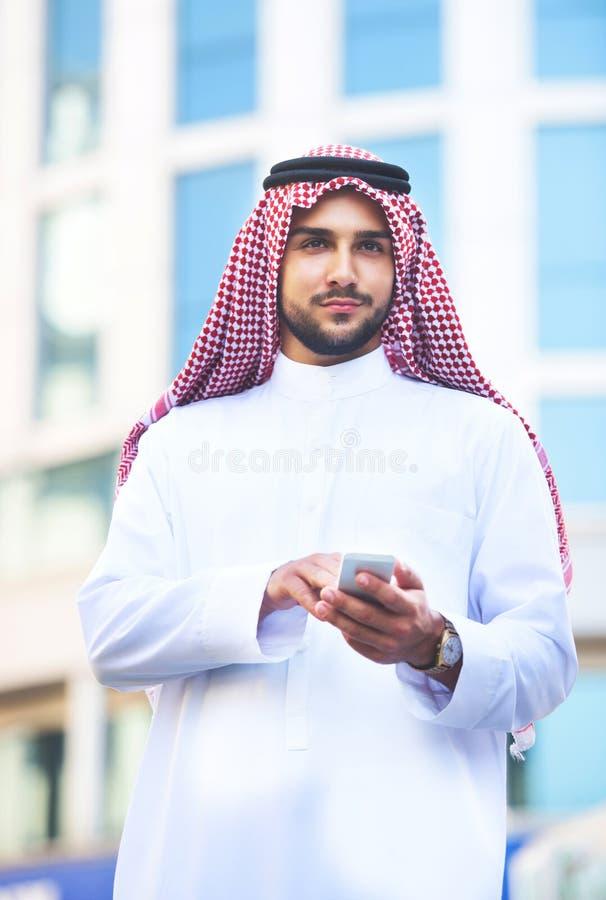 Retrato de um homem árabe considerável que usa um telefone esperto foto de stock