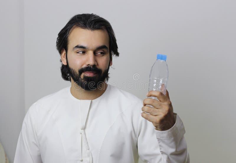 Retrato de um homem árabe que guarda uma garrafa de água substituível fotos de stock royalty free