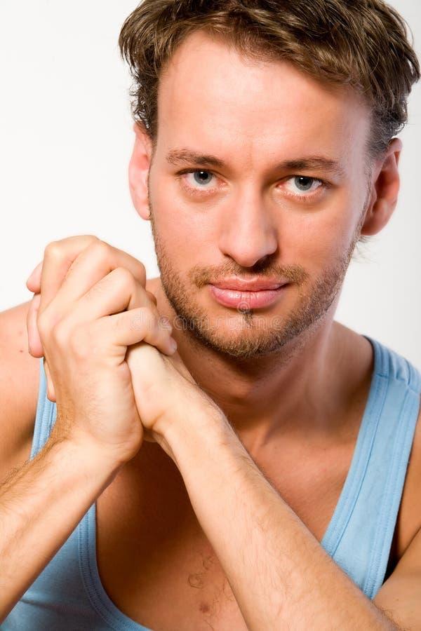 Retrato de um homem adulto novo em uma camisa azul fotografia de stock