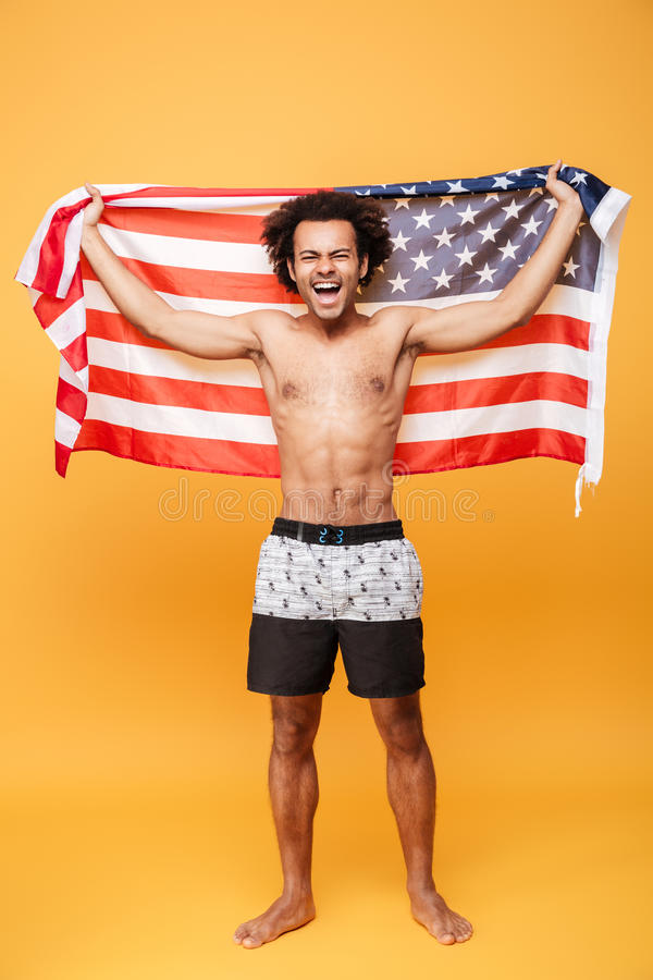 Retrato de um homem africano entusiasmado feliz que guarda a bandeira dos E.U. fotos de stock royalty free