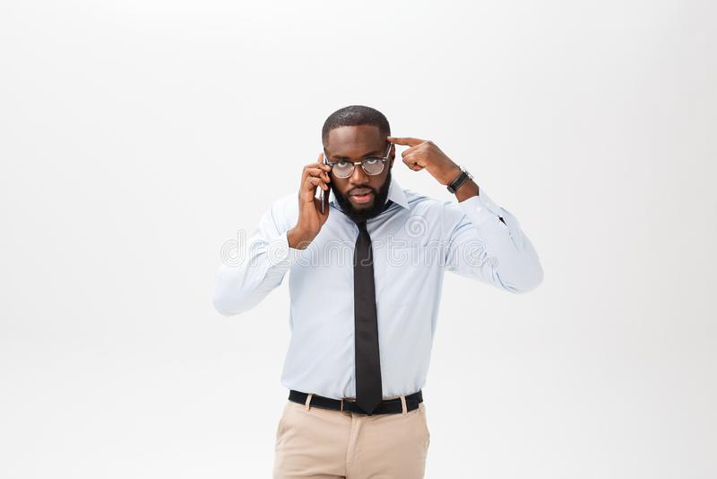 Retrato de um homem africano novo confuso vestido na camisa branca que fala no telefone celular e em gesticular isolados sobre foto de stock royalty free