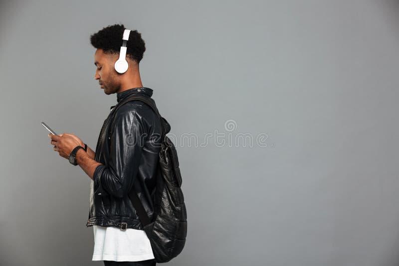 Retrato de um homem afro-americano novo nos fones de ouvido fotografia de stock royalty free