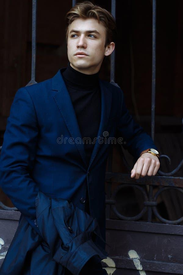 Retrato de um homem atrativo, indivíduo, homem de negócios, olhando a câmera, vestindo um terno azul, guardando um relógio de our foto de stock royalty free