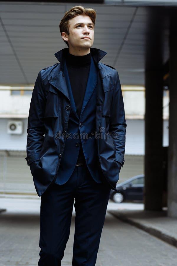 Retrato de um homem atrativo, indivíduo, homem de negócios, vestindo um terno azul, um revestimento Mãos em uns bolsos, valor na  foto de stock