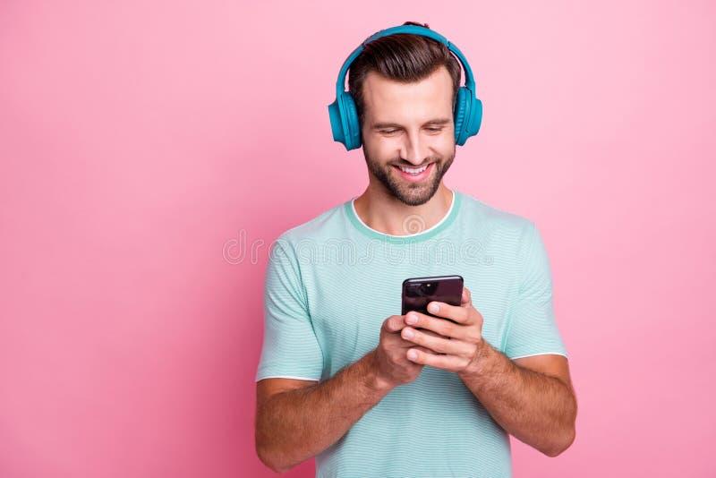 Retrato de um homem de boa alegria que amava música escuta músicas de rádio usam fones de ouvido navegando na internet escolher imagem de stock royalty free