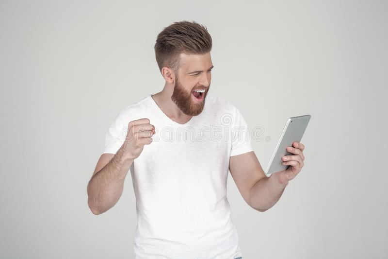 Retrato de um homem bonito com uma barba e um penteado elegante, vestido na roupa ocasional gritando felizmente na tabuleta, foto de stock