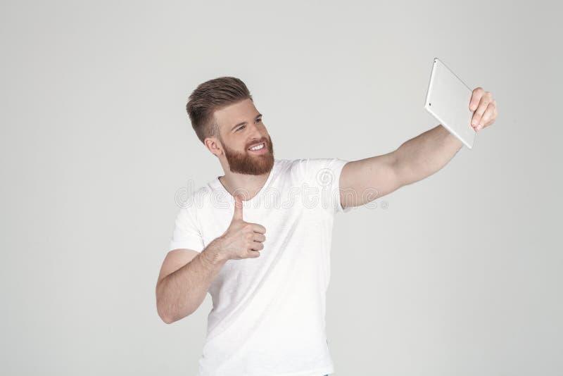 Retrato de um homem bonito com uma barba e um penteado elegante vestidos na roupa ocasional fazendo um sephi em sua tabuleta e fotos de stock royalty free
