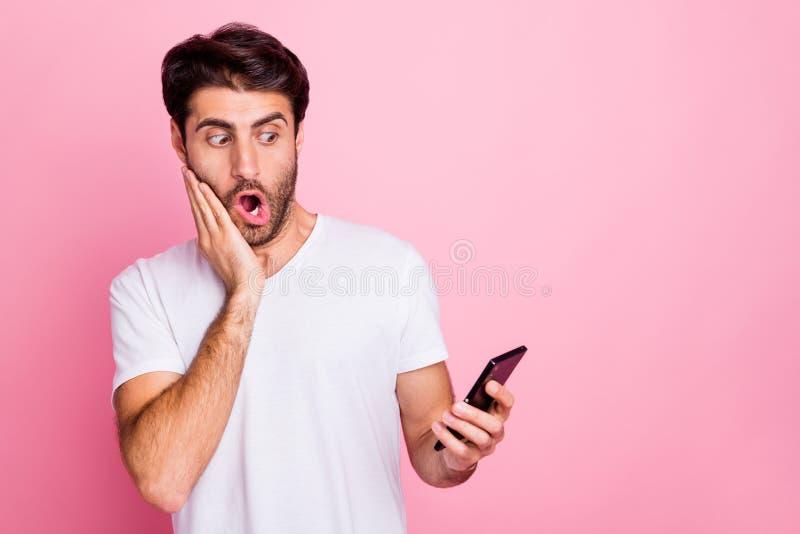 Retrato de um homem bonito e chocado, do Oriente Médio, use celulares para ver informações para ler e obter um feedback terrível imagem de stock
