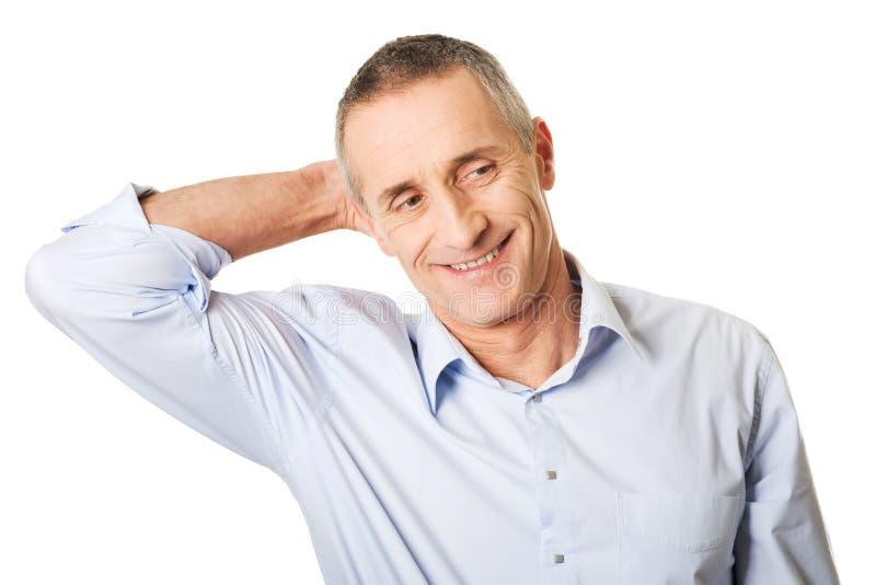 Retrato de um homem bonito que toca em sua cabeça foto de stock