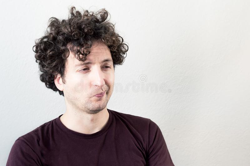 Retrato de um homem de cabelo novo, caucasiano, triguenho, encaracolado com expressão do desagrado no fundo branco fotografia de stock royalty free