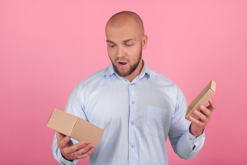 Retrato de um homem calvo bonito com uma barba vestida em uma camisa branca abre um presente com emo??es chocantes suportes na fr foto de stock