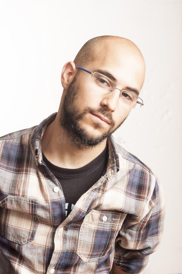 Retrato de um homem calvo novo com uma barba e vidros foto de stock