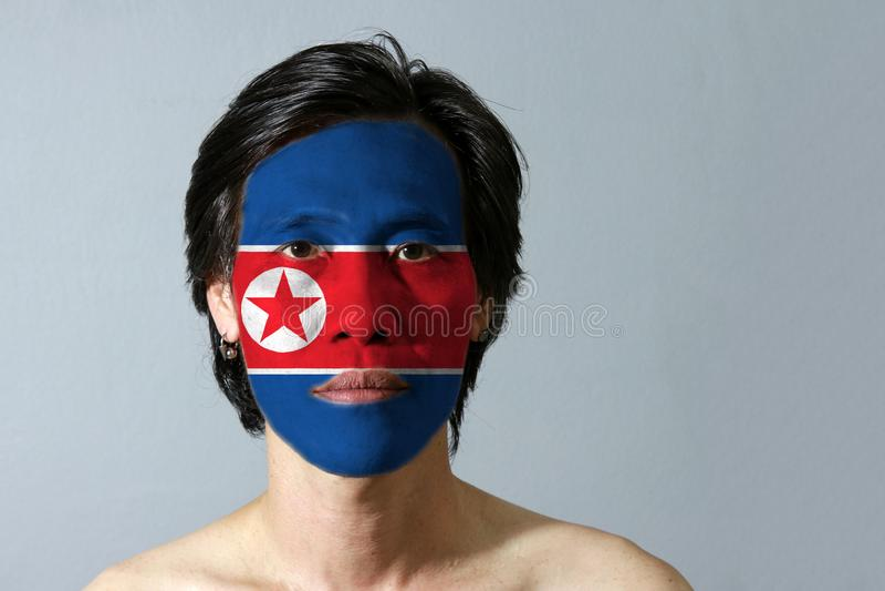 Retrato de um homem com a bandeira da Coreia do Norte pintada em sua cara no fundo preto imagem de stock