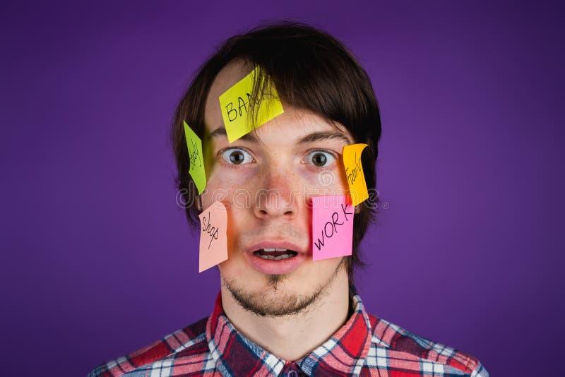 Retrato de um homem com etiquetas em seus olhares da cara surpreendido na câmera, um homem em choque da rotina diária imagens de stock
