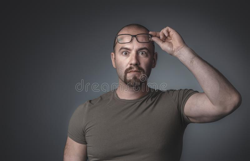 Retrato de um homem com expressão surpreendida que aumenta seus vidros fotos de stock