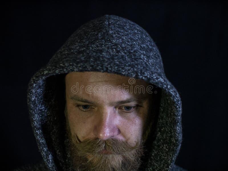 Retrato de um homem com uma barba e do bigode na capa com uma cara s?ria em um fundo preto fotos de stock royalty free