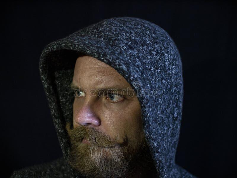 Retrato de um homem com uma barba e do bigode na capa com uma cara s?ria em um fundo preto foto de stock