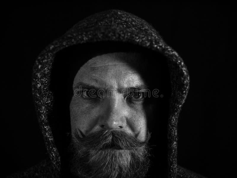 Retrato de um homem com uma barba e do bigode na capa com uma cara s?ria em um fundo preto Pequim, foto preto e branco de China imagens de stock