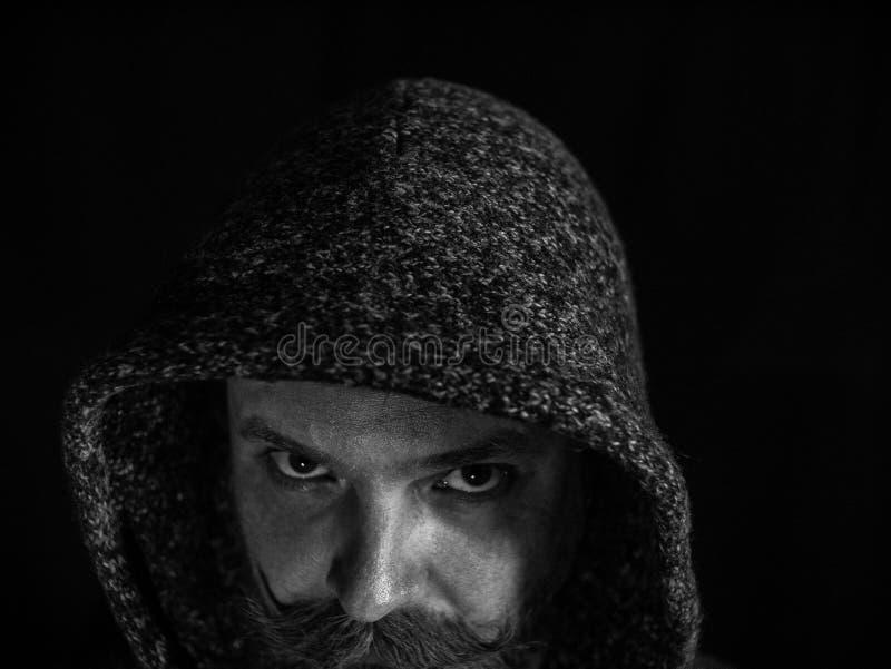 Retrato de um homem com uma barba e do bigode na capa com uma cara s?ria em um fundo preto Pequim, foto preto e branco de China fotografia de stock