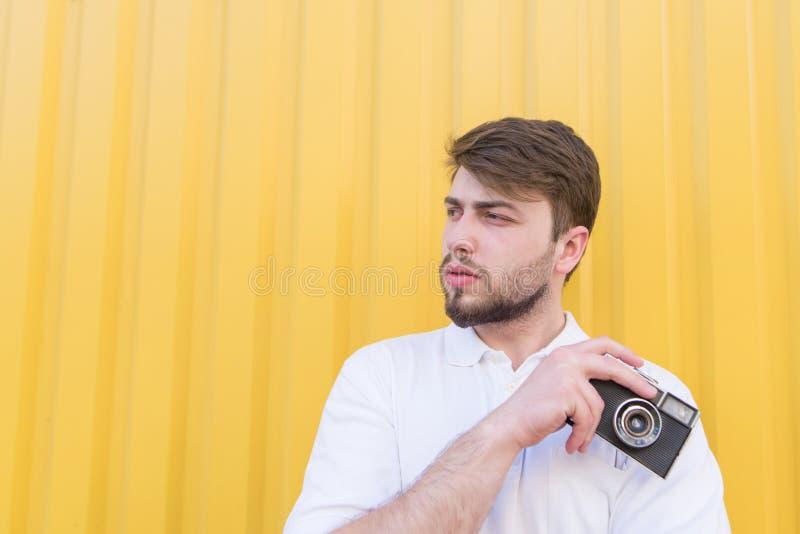 Retrato de um homem com uma câmera retro em suas mãos em um fundo amarelo fotografia de stock