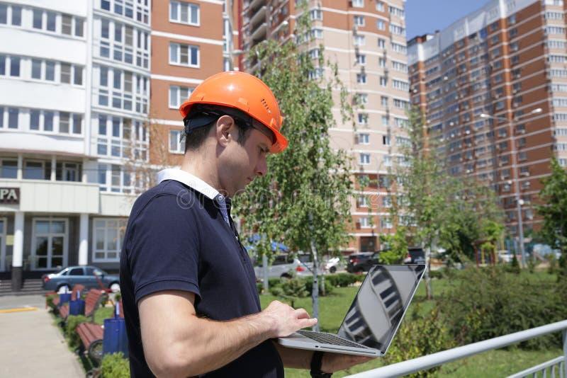 Retrato de um homem considerável novo em um capacete protetor com um portátil em suas mãos na frente de uma construção alta foto de stock royalty free