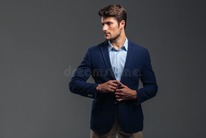 Retrato de um homem considerável ocasional que abotoa seu revestimento imagens de stock