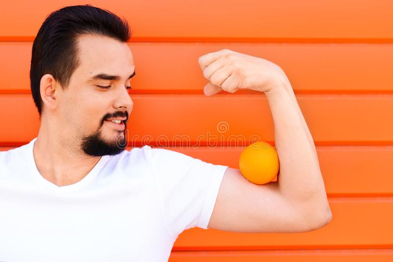 Retrato de um homem considerável de sorriso com bigode e da barba que mantém uma laranja em seu músculo do bíceps contra a parede foto de stock royalty free