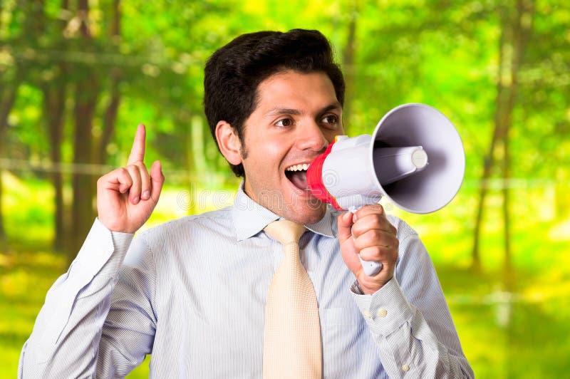 Retrato de um homem considerável de sorriso que fala com um megafone em um fundo verde borrado imagens de stock royalty free
