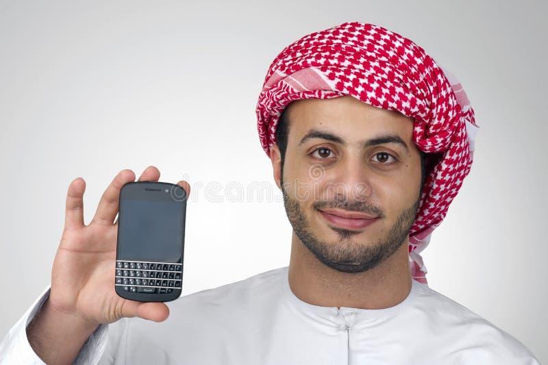 Retrato de um homem de negócio árabe que guarda um telefone para a apresentação imagens de stock royalty free