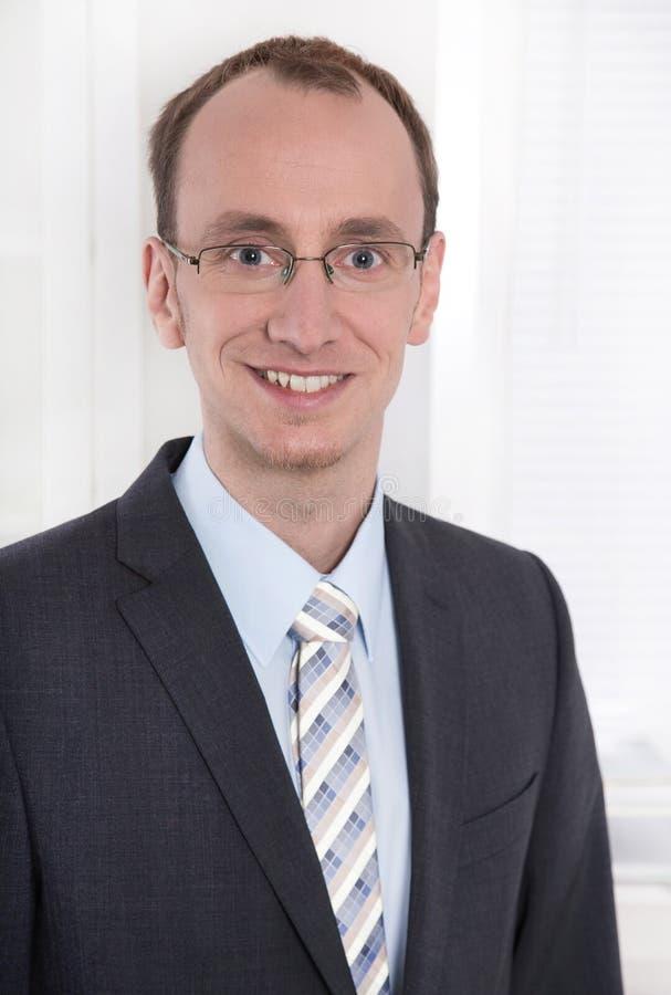 Retrato de um homem de negócios de sorriso novo ou coordenador com vidros fotografia de stock royalty free