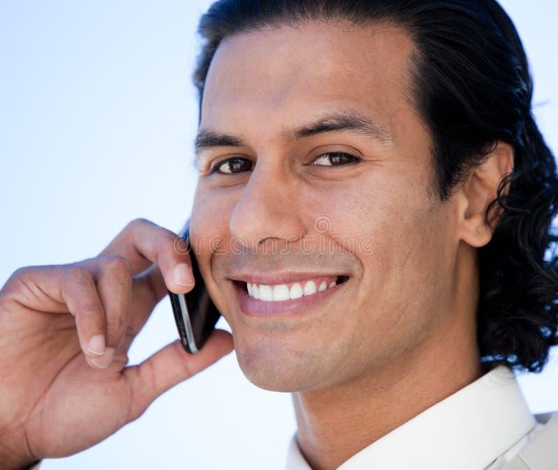 Retrato de um homem de negócios latino-americano feliz no telefone foto de stock