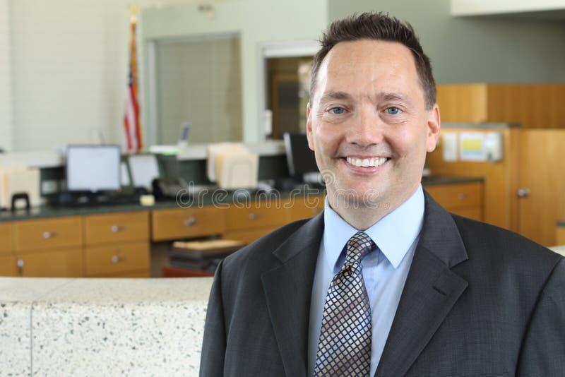 Retrato de um homem de negócios (maduro) superior que está no escritório e no sorriso imagem de stock