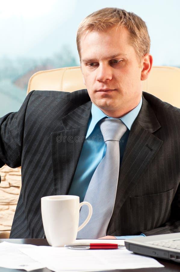 Retrato de um homem de negócios novo na dúvida sobre o som fotografia de stock