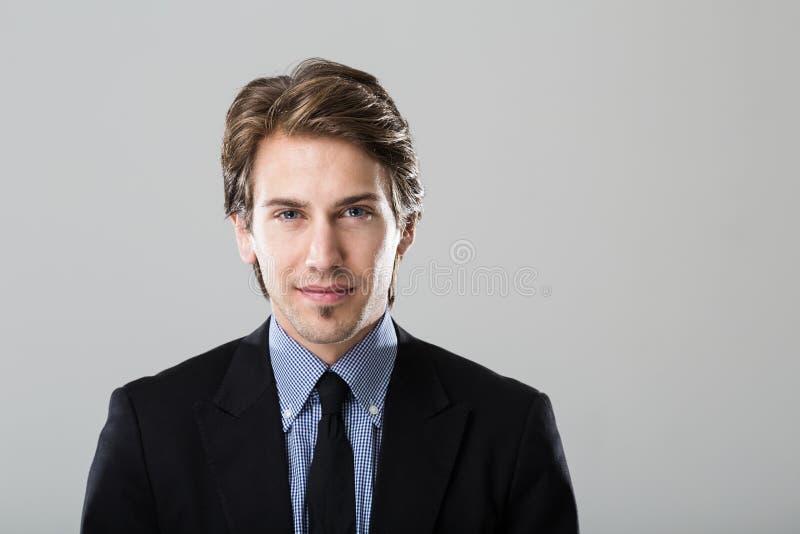 Retrato de um homem de negócios novo no fundo cinzento imagem de stock