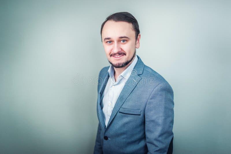 Retrato de um homem de negócios novo no fundo cinzento foto de stock royalty free