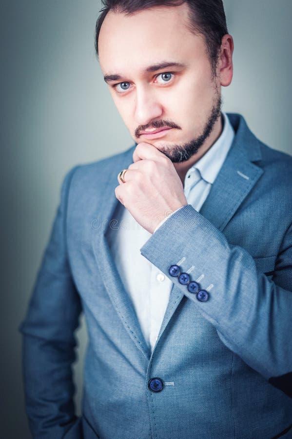 Retrato de um homem de negócios novo no fundo cinzento foto de stock