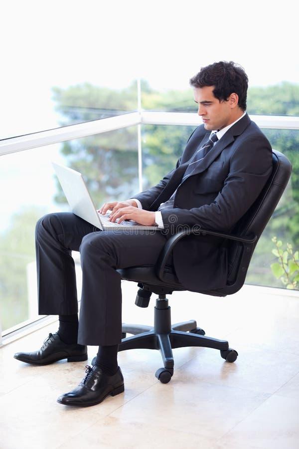 Retrato de um homem de negócios que senta-se em um funcionamento da poltrona   imagem de stock royalty free