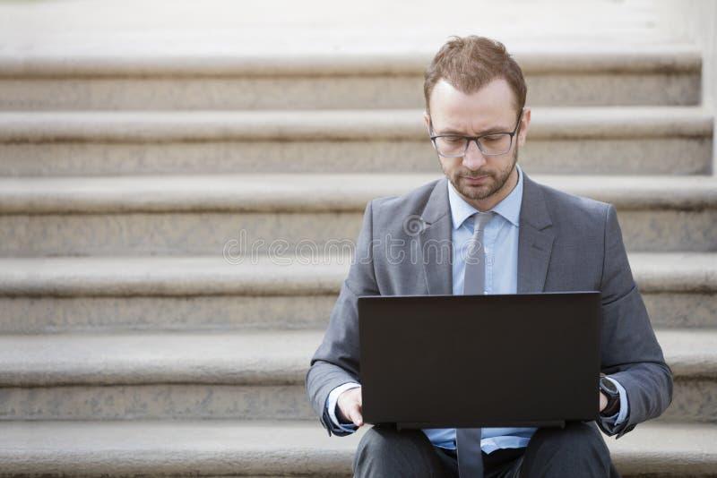 Retrato de um homem de negócios que senta-se nas escadas e que trabalha em l fotos de stock royalty free